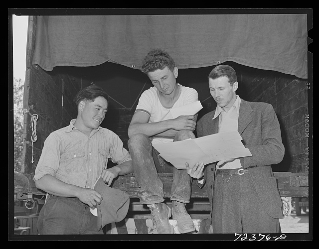 Los Angeles County, California. The evacuation of Japanese-Americans from West coast areas under United States Army war emergency order. FSA (Farm Security Administration) representative (right) talking with two farmers, one white and one Japanese. They are discussing the sale of the farm equipment, belonging to the Japanese, to the white farmer