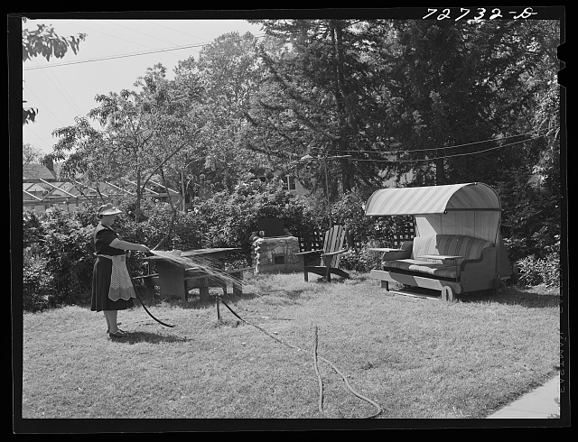 Turlock, California. Housewife waters the lawn. All garden furniture and barbecue pit were made by her husband; about one out of every three houses in this town has such an arrangement in the backyard, and during the summer months people eat and spend many hours in their yards