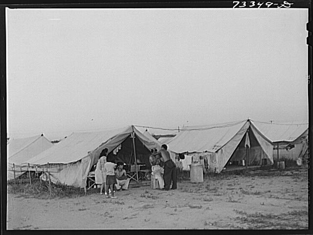 Nyssa, Oregon. FSA (Farm Security Administration) mobile camp. Ordinarily electricity is not supplied to the tents of migrant families living in the FSA camps. These Japanese-Americans, who were accustomed to better living conditions, wanted the electricity and the sugar beet companies and the town of Nyssa arranged for the wiring. Some of the wiring is the Christmas tree light wiring from Nyssa