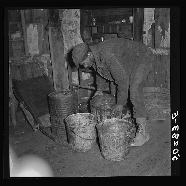 A neighbor (coal miner) taking away some slops for his pigs. Bertha Hill, West Virginia