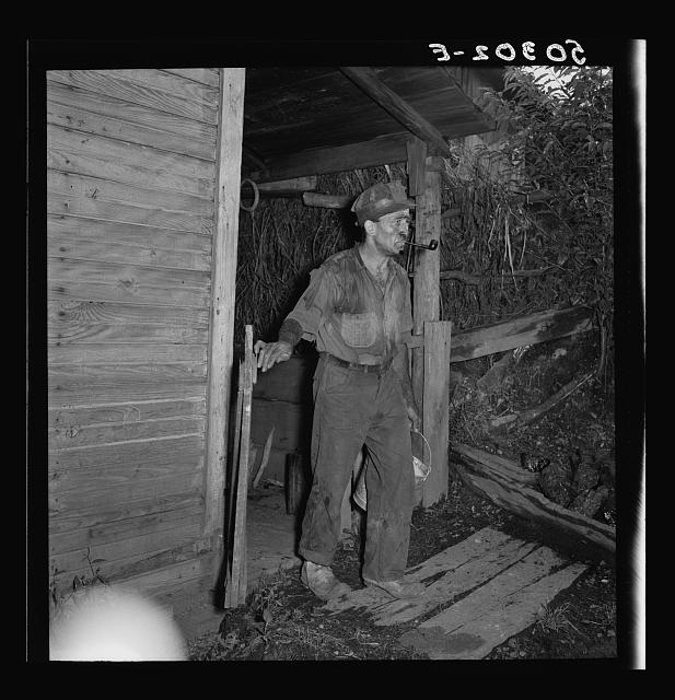 "Coal miner going to get some water down the hill from his home. ""The Patch,"" Chaplin, West Virginia"