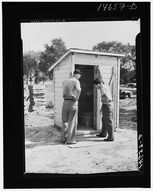 Completed sanitary privy in Minnesota being inspected by farmer and engineer of Farm Security Administration. Minnesota