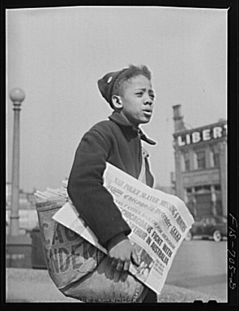 Chicago, Illinois. Newsboy selling the Chicago Defender, a leading Negro newspaper