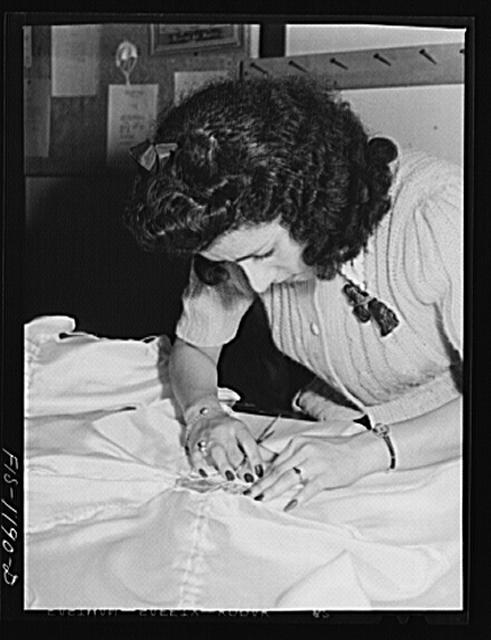 Mexican girl inspecting the shrouds or briddle of a pilot parachute made at the Pacific Parachute Company. San Diego, California