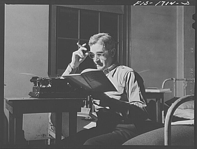 Chaplain Anthony J. O'Driscoll, Order of Friars Minor Franciscan, studying for an examination in the morning. U.S. Army chaplain school, Fort Benjamin Harrison, Indiana