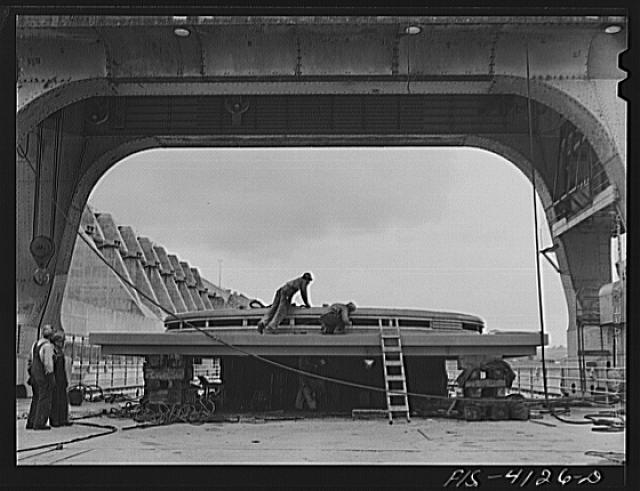 Cherokee Dam, Tennessee (Tennessee Valley Authority (TVA)). Working on the cover of a 30,000 kilowatt generator under a 250 ton gantry crane
