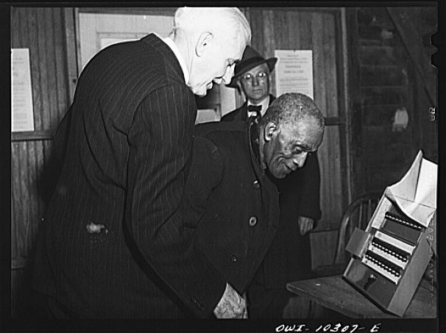 Olney, Maryland. Showing a Negro how to vote at the polls on election day