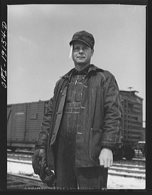 Argentine, near Kansas City, Kansas. Floyd C. McKillip, switchman, in the Atchison, Topeka and Santa Fe Railway yards. The paper stuck in his cap is a switch list