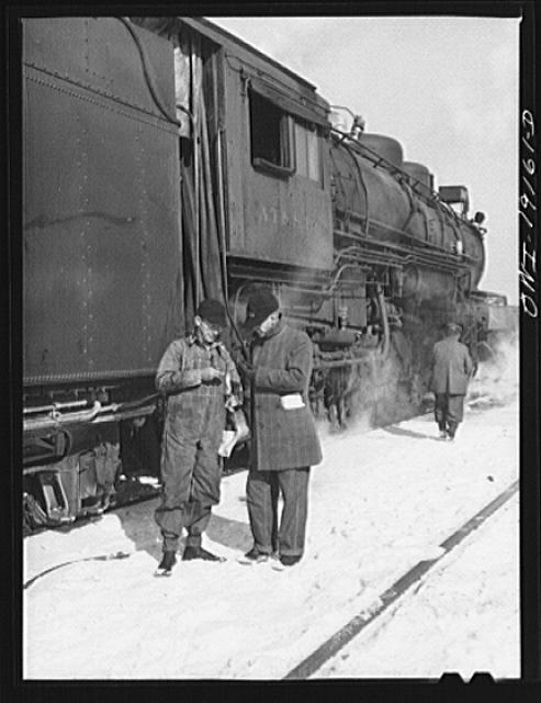Chicago, Illinois. Atchison, Topeka and Santa Fe Railroad conductor George E. Burton and engineer J.W. Edwards comparing time before pulling out of Corwith Railroad yard for Chillicothe, Illinois