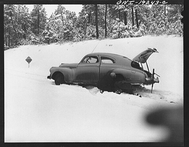 Penasco, New Mexico. Doctor Onstine, seventy-seven year old country physician, putting chains on his car to get from Taos to the clinic operated by the Taos County cooperative health association