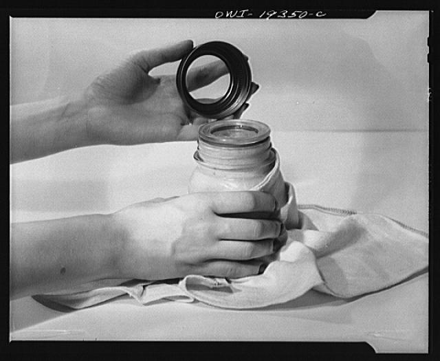 Steel-saving glass-top jars recommended by the War Production Board, Containers Division, for home canning of the Victory garden fruits and vegetables in 1943. Second step is to place the lid directly on top of the ring on the jar mouth, which must be smooth, even, and clean. To make a snug seal, lid and ring are screwed down with the threaded steel band