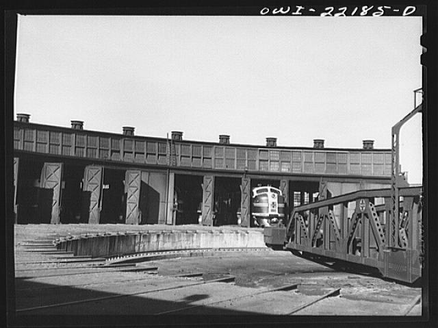 Winslow, Arizona. Atchison, Topeka and Santa Fe Railroad diesel freight engine coming out of the roundhouse. The entire engine consists of four units, only two of which can be accomodated in a stall at the roundhouse or on the turntable