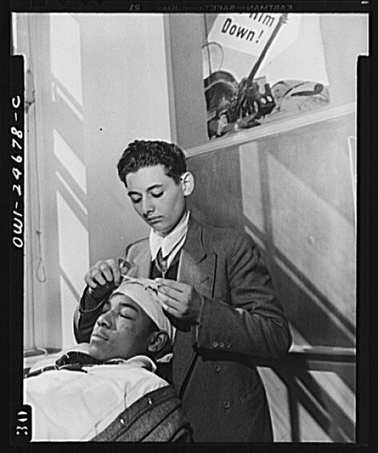 "Benjamin Franklin High School, New York, New York. Boys take one day a week from their English course for ""war activities"" in order to learn the basic principles of first aid"