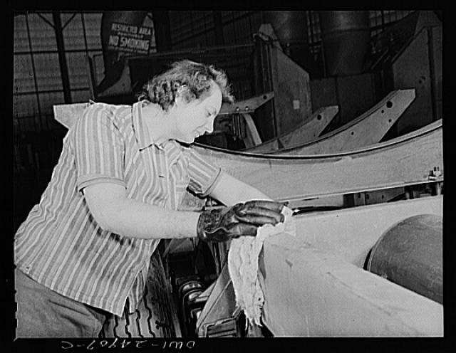 Milwaukee, Wisconsin. War production workers at the Heil Company making gasoline trailer tanks for the U.S. Army Air Corps. Irean Smotinski, age twenty-nine, and ex-housewife, cleaning a chassis before it goes to the paint room
