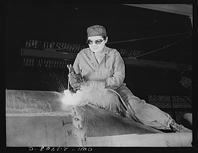 Milwaukee, Wisconsin. War production workers at the Heil Company making gasoline trailer tanks for the U.S. Army Air Corps. Enola O'Connell, age thirty-two, widow and mother of one child, welding part of a trailer. She is the only woman welder in the plant. This is her first job outside her house