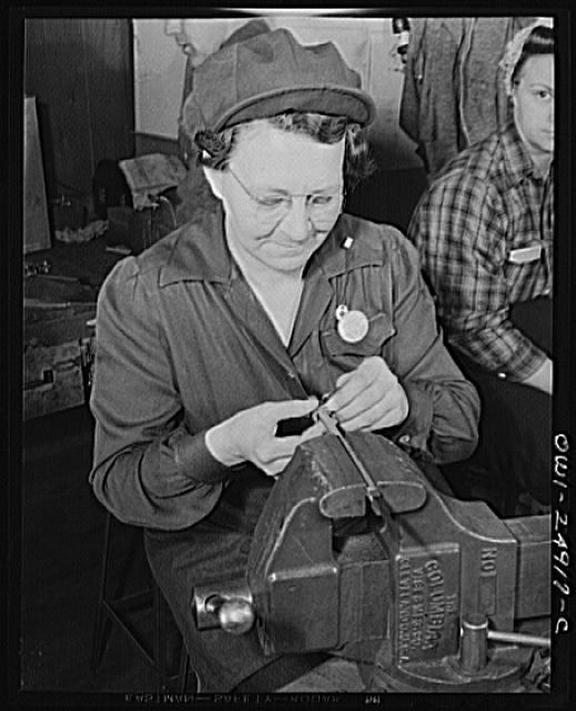 Milwaukee, Wisconsin. War production workers making M5 and M7 guns for the U.S. Army. Ex-housewife, age forty-nine, filing small parts. Her son and son-in-law are in the armed service