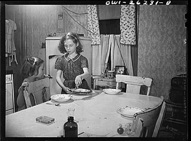 Buffalo, New York. Beverly Ann Grimm, eleven, serving an omelette for Saturday lunch for her sisters and herself, while Pasty looks on. Their mother, a twenty-six year old widow, is a crane operator at Pratt and Letchworth
