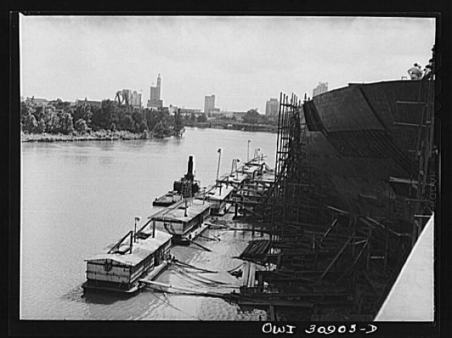 Beaumont, Texas. Cargo vessels under construction at the Pennsylvania shipyards; welding barges are moored in the foreground