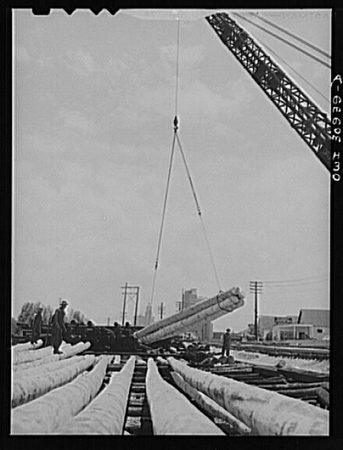 Beaumont, Texas. Crane picking up properly aged poles which will be treated in vats at the International Creosoting Company