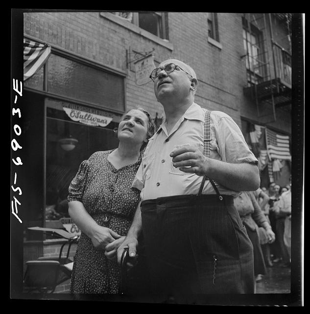 New York, New York. Italian-Americans in the rain watching a flag raising ceremony in honor of the feast of San Rocco at right
