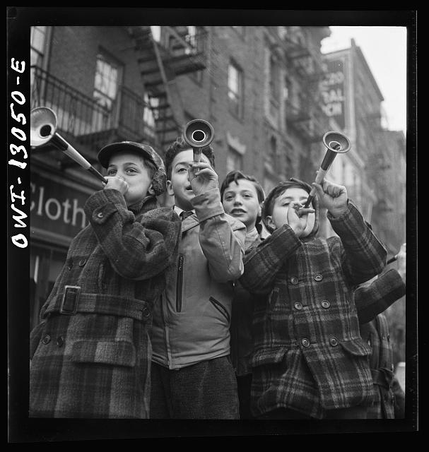 New York, New York. Blowing horns on Bleeker Street on New Year's Day