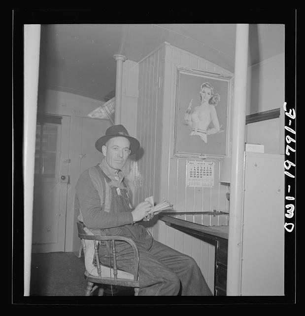 Conductor G. Reynolds, checking his waybills in the caboose of the Atchison, Topeka, and Santa Fe Railroad between Argentine and Emporia, Kansas