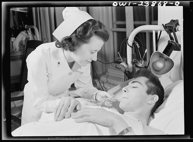 Encased in a body and leg cast, this soldier must have constant care. Here, Army nurse Frances Bullock helps him to a drink of fruit juice