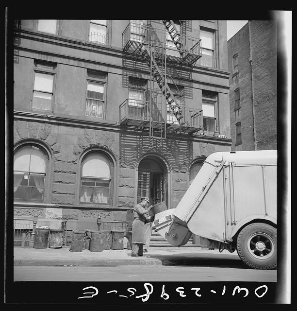 New York, New York. Emptying garbage and trash from Harlem apartment houses