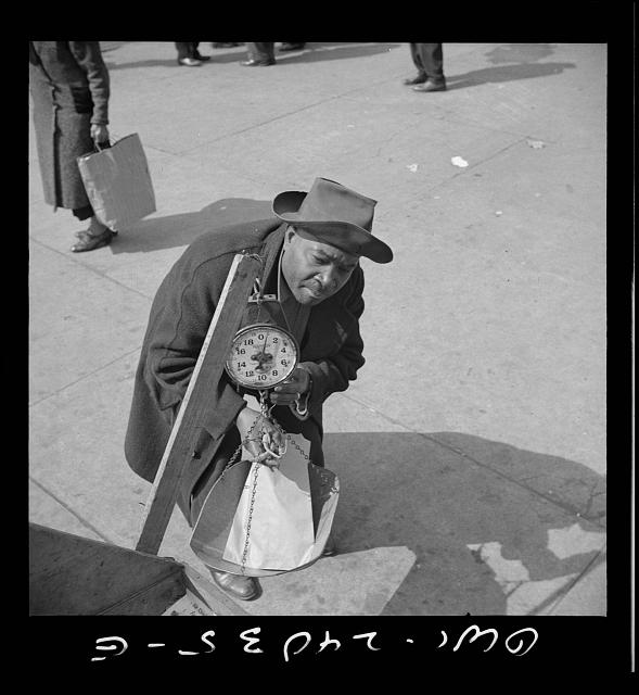 New York, New York. Street peddler in Harlem weighing string beans