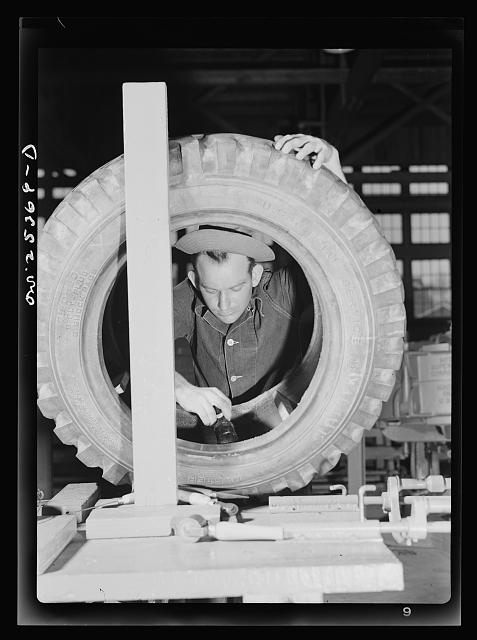 Holabird ordnance depot, Baltimore, Maryland. A soldier cementing the inner side wall of a truck tire; he is preparing this tire for sectional repair in the recapping shop