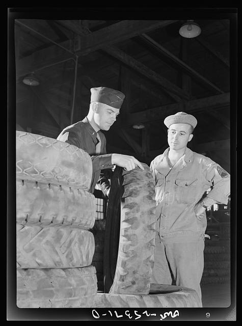 Holabird ordnance depot, Baltimore, Maryland. Lieutenant George Sundstrom, San Bernardino, California, and Staff Sergeant Harold Creasap, Akron, Ohio, inspecting an Army truck tire which has been brought to the recapping shop. All tires are given this preliminary visual inspection