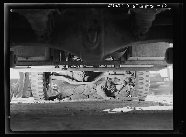 Holabird ordnance depot, Baltimore, Maryland. Periodic complete vehicle inspection is required of every United States Army driver. This soldier is checking the wheel alignment of his truck, one of the most important factors in the length of life of tires