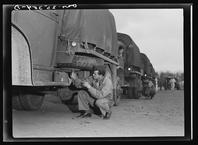 "Holabird ordnance depot, Baltimore, Maryland.  A soldier checking the air pressure on his spare tire. The gages are called ""fiddlesticks"""