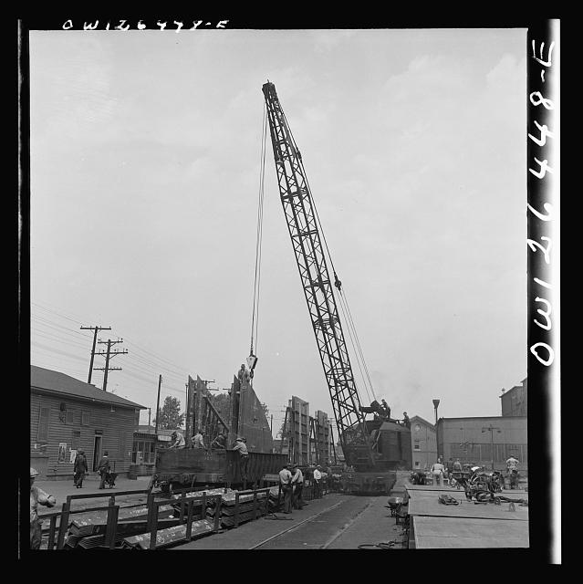 Bethlehem-Fairfield shipyards, Baltimore, Maryland. Transferring a steel section from the fabricating table to a railroad car