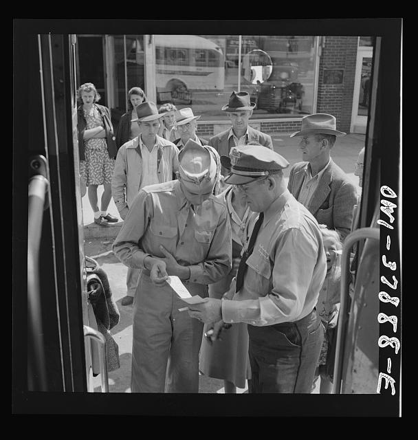 A Greyhound bus trip from Louisville, Kentucky, to Memphis, Tennessee, and the terminals. Soldier checking ticket with the bus driver before getting on at a small town in Georgia