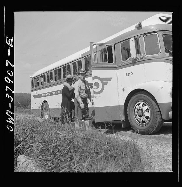 A Greyhound bus trip from Louisville, Kentucky, to Memphis, Tennessee, and the terminals. Greyhound driver helping woman with her bag. From a nearby farm, she flagged the bus on the highway