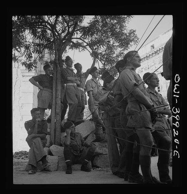 Allied soldiers and Sicilian civilians listening to a band concert