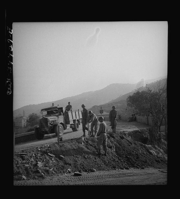 British equipment and troops repairing Sicilian roads demolished by the Germans
