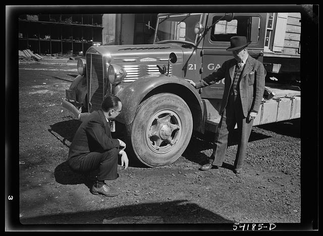 Washington, D.C. A Galliher and Huguely, Inc. truck, showing two men looking at one of the tires