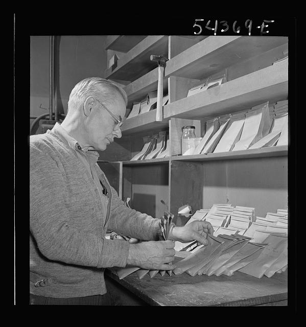 Kingman (vicinity), Arizona. A laboratory worker at a recovery plant near the Boriana mine selecting a sample of tungsten ore