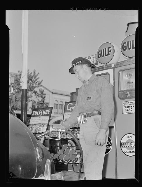 Gas station attendant at service station filling tank of a motorist's Dodge car. Washington, D.C.