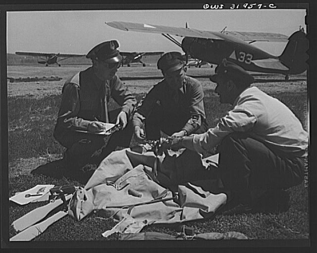 "Bar Harbor, Maine. Civil Air Patrol base headquarters of coastal patrol no. 20. Intelligence officer checking safety equipment issued to the pilot and observer of a patrol plane, including rubber boat and life jacket ""Mae West,"" inflatable by carbon dioxide gas catridges; repair kit to mend bullet in the boat; and dye container to color water for better identification; flashlight with red lens for identification by night; smoke bombs; water markers; Very pistols; and rubber watertight flying suit"