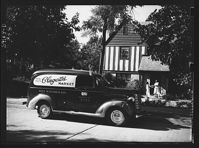 Washington, D.C. A Clagett Market delivery truck displaying a United States Truck Conservation Corps pledge standing in front of a residence where the driver is handing a basket of groceries to a colored maid