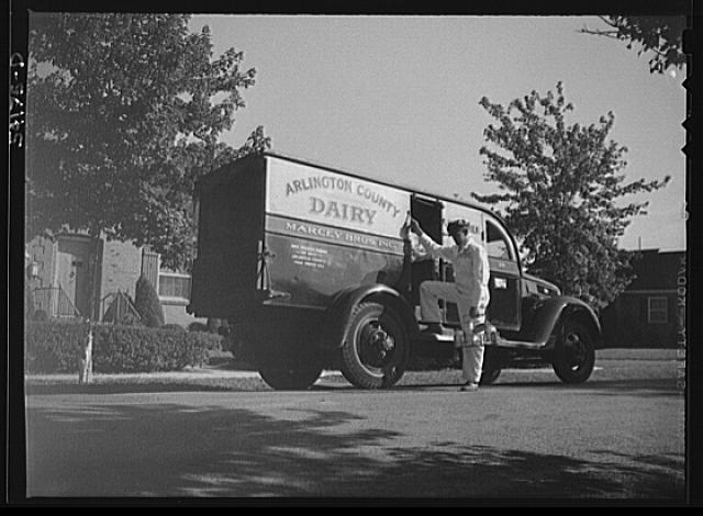 Arlington (?), Virginia. Arlington County dairy truck from which a driver is alighting with a tray of milk bottles. On the door of the truck is displayed a United States Truck Conservation Corps pledge