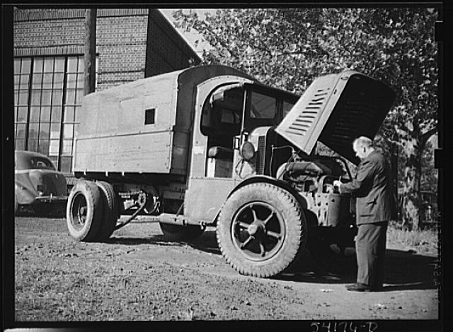 Washington, D.C. A man looking at the motor of a commercial truck on the side of which is displayed a United States Truck Conservation Corps pledge