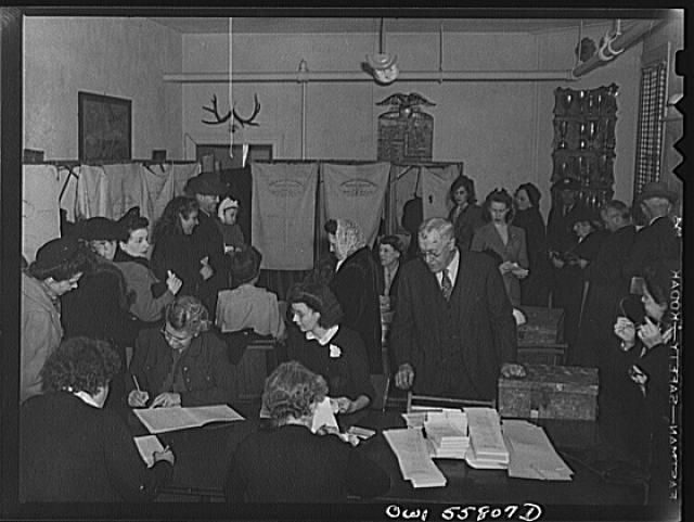 "Arlington, Virginia. Interior of the firehouse with firemen's trophies in the background. Citizens' names are checked to see that each has paid his poll tax and registered. Ballots for the national presidental election are presented to each for secret voting in the ""Douglas Collapsible"" booths, and the ballots are dropped in boxes"