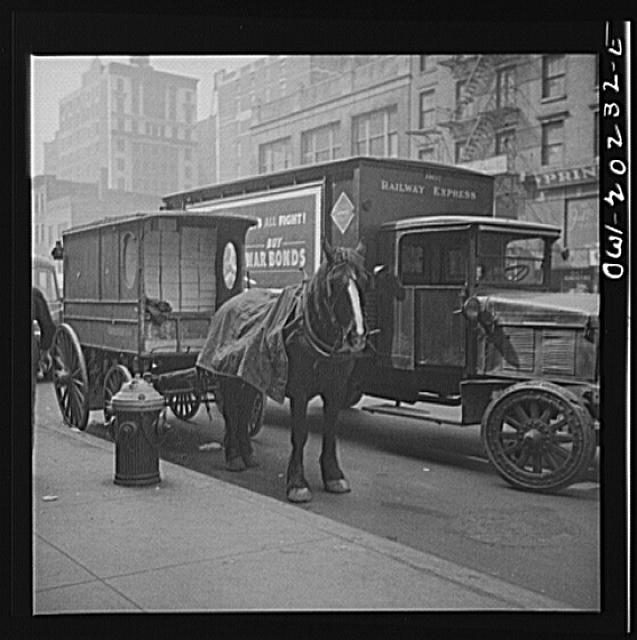 New York, New York. A horse and wagon and a railway express truck