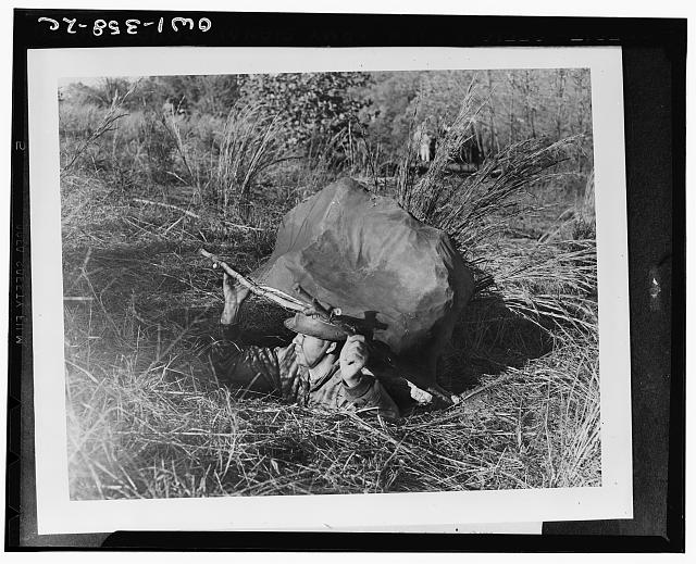 Private William Madison emerging from a foxhole concealed by a papier mache rock during a camouflage demonstration