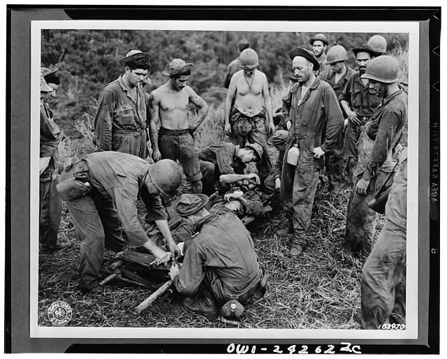 A casualty from the front line fighting is being transferred from the makeshift stretcher before being taken through jungle and down river to near hospital. Guadalcanal