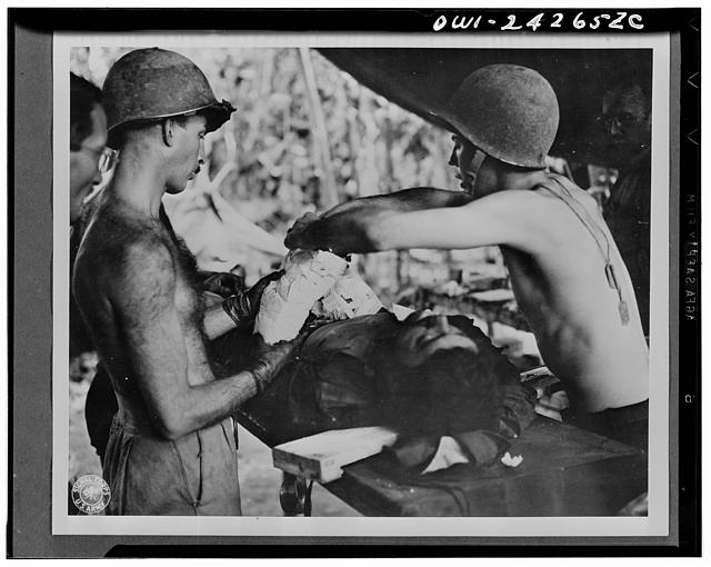 An operation on wounded American soldier is performed by Major George Marks. The soldier has been wounded in the arms and shoulders by shrapnel from a Jap mortar as he was storming a pillbox in New Guinea